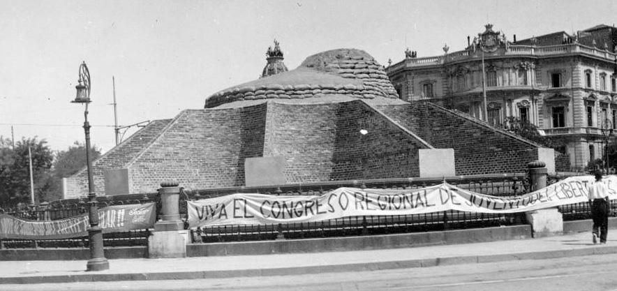 """Aspecto de la Fuente de CIbeles, sepultada bajo una """"pirámide"""" de ladrillos y sacos de arena, para protegerla durante la Guerra Civil."""
