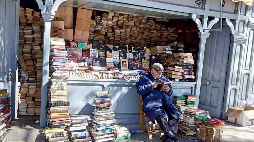 Propietario de una de las librerías de la Cuesta de Moyano, aprovechando el tiempo con un buen libro.