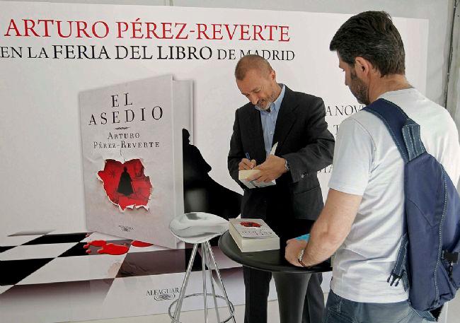 El popular escritor Arturo Pérez Reverte durante la firma de libros en la Feria del Libro de Madrid.