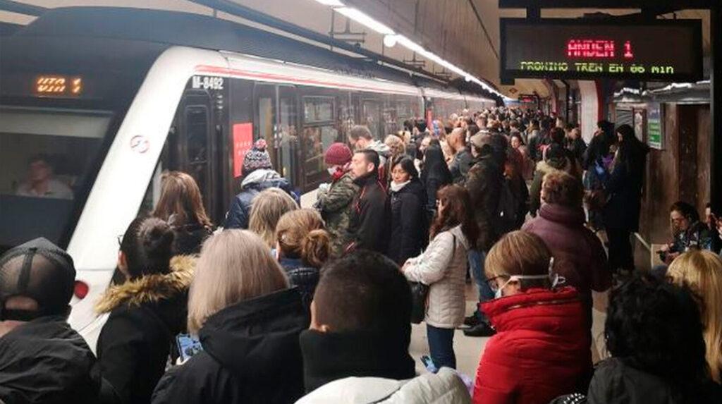 Detalle de un abarrotado andén del Metro de Madrid con el luminoso que indica el tiempo que queda para el próximo tren.