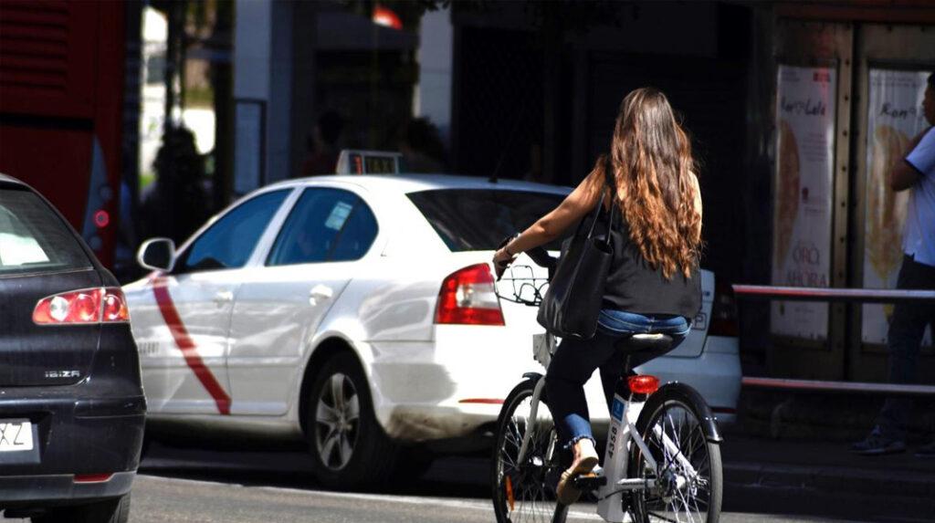 Una usuaria de BiciMAD circula con la bicicleta por una de las calles de la ciudad.