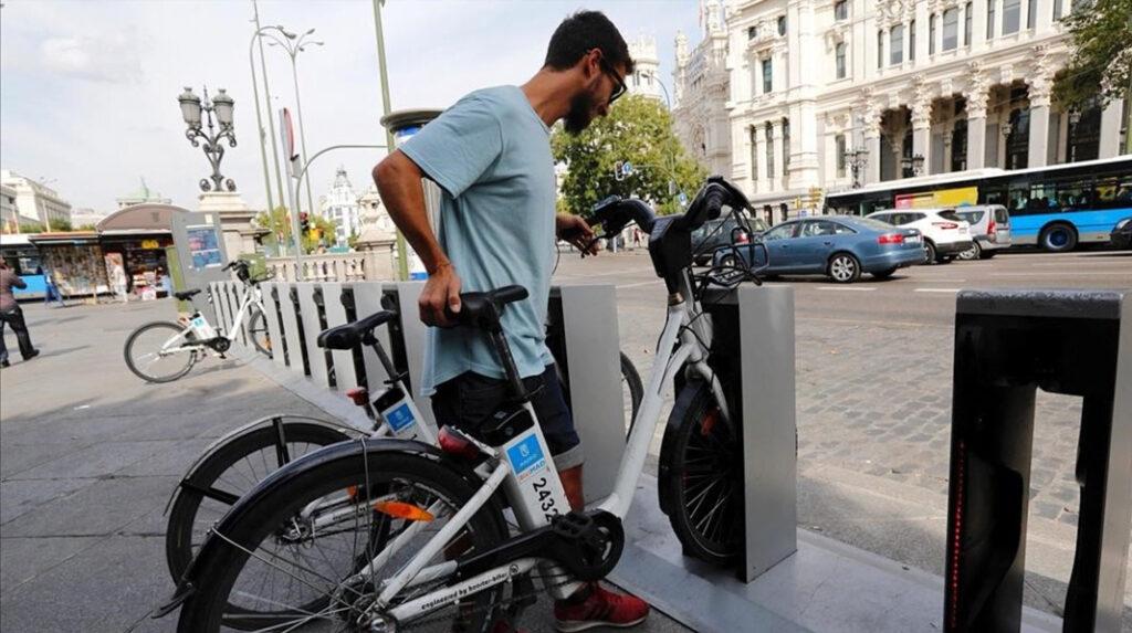 Un usuario coloca una de las bicicletas eléctricas de BiciMAD en la estación.