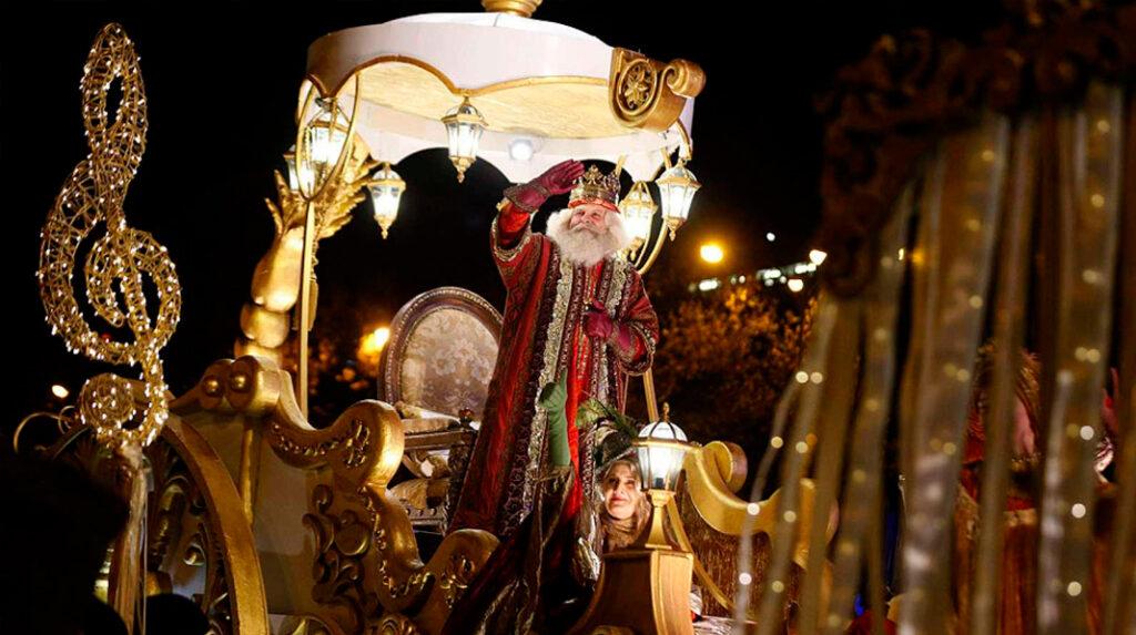 Melchor, uno de los Reyes Magos, paseando en su carroza por las calles de Madrid.