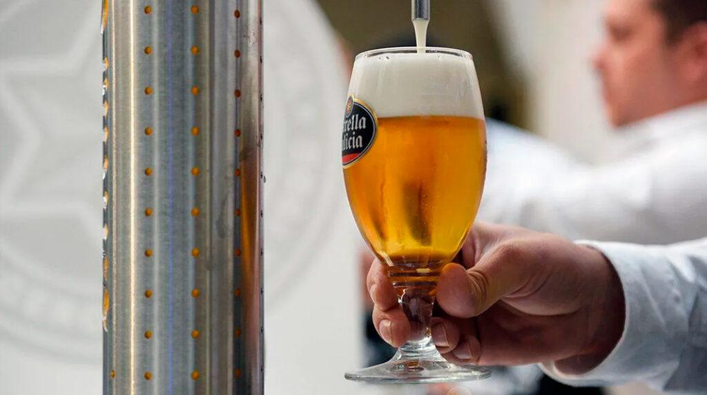 Camarero sirviendo un doble de cerveza en copa.