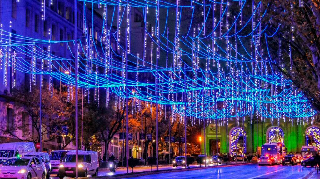 La calle de Alcalá iluminada por Navidad, con la Puerta de Alcalá al fondo también iluminada.