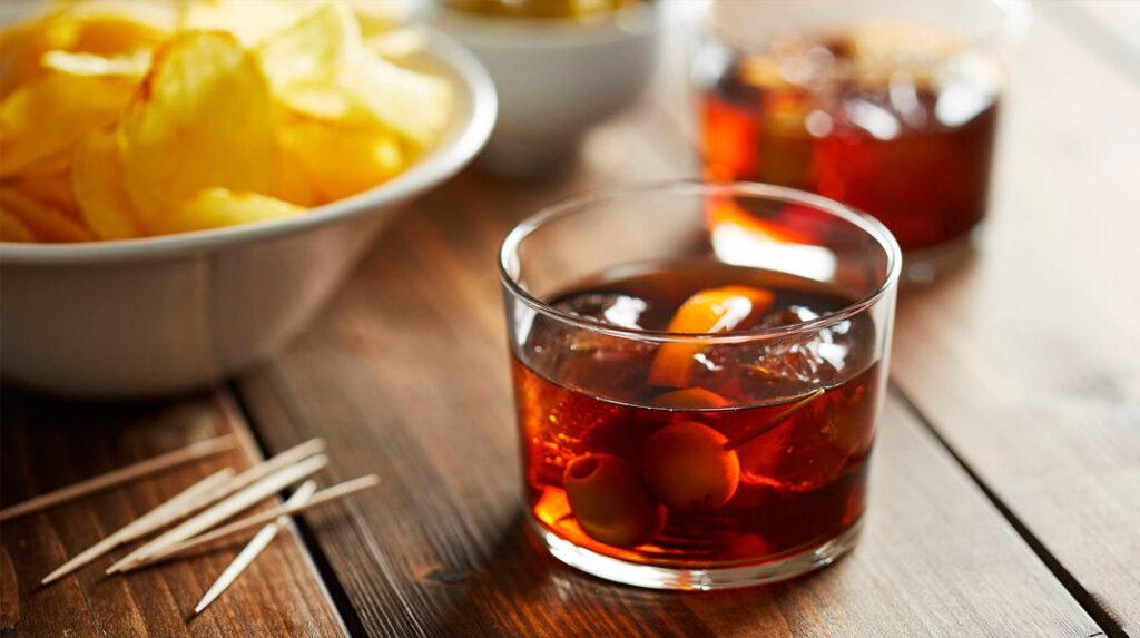 Clásico Vermú, servido en vaso, con hielo, media rodaja de naranja y aceitunas.