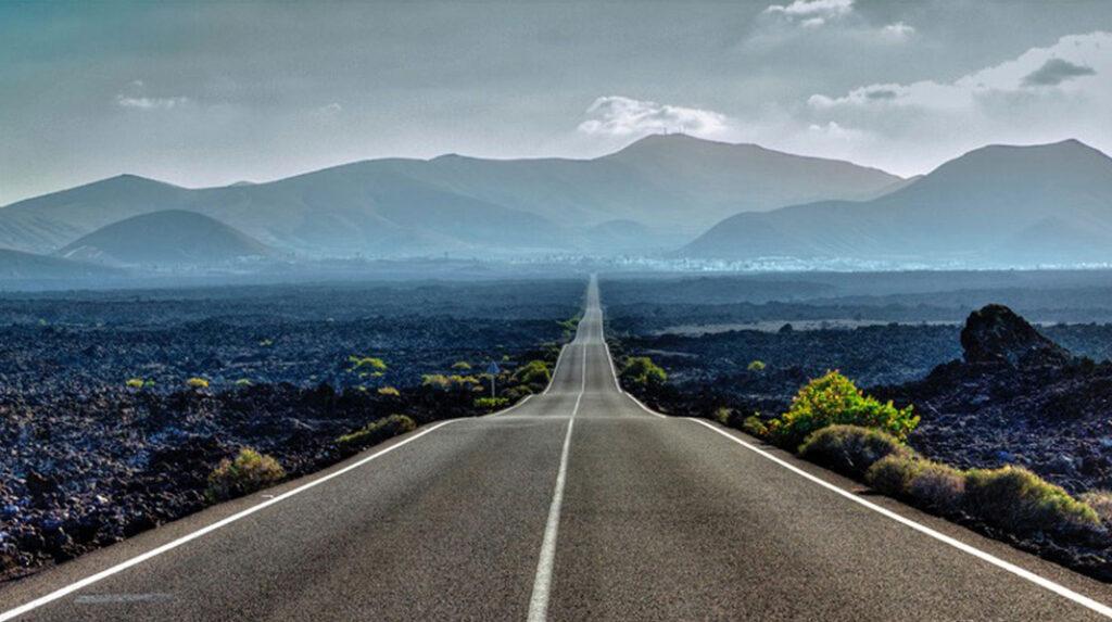 Típica carretera de Lanzarote, de trazado recto y rodeada de lava, con una zona volcánica al fondo.