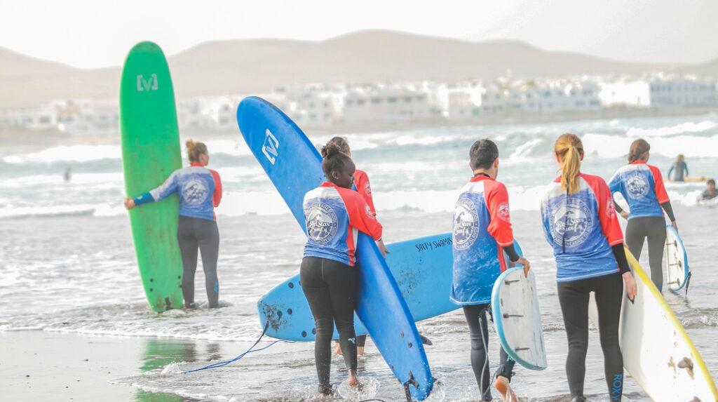 Jóvenes aprendiendo surf con una de las numerosas escuelas de Playa de Famara.
