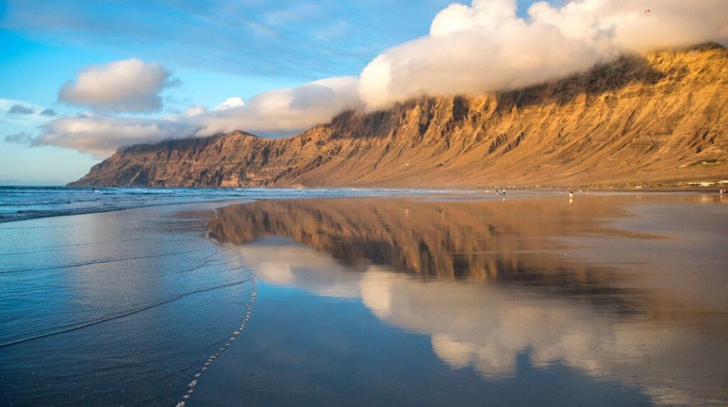 Característico reflejo del risco de Famara en el agua durante la marea baja en la playa del mismo nombre.