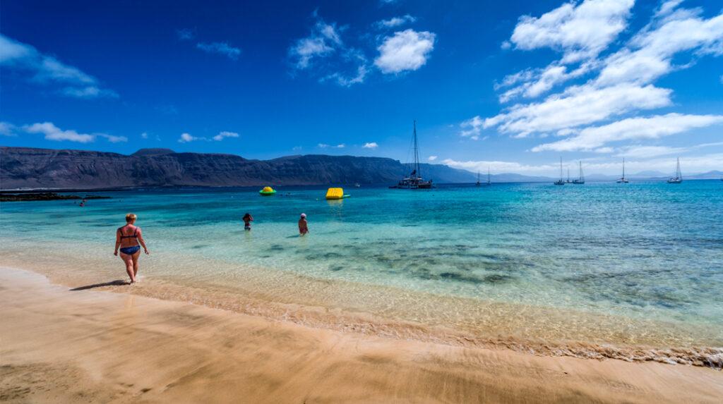 Playa de La Francesa, con los barcos de recreo fondeados y los acantilados de Famara al fondo.