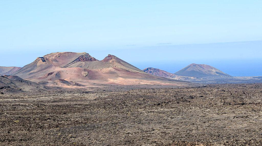 Vista de las Montañas de Fuego tras un llano de lava solidificada.